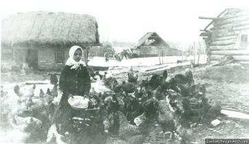 A young Ukrainian girl feeds the chickens on her parents' farm close to Usherville. Photo credit: saskarchives.com